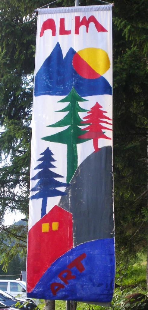 AlmART Fahne am Parkplatz Pommer