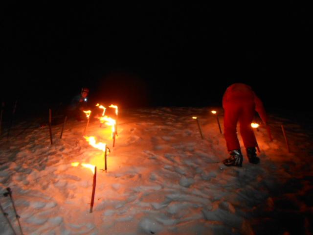Brennende Fackeln im Schnee hinter dem Alpengasthof Lämmerhof