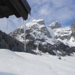 Eiszapfen am Dach mit Bergkulisse